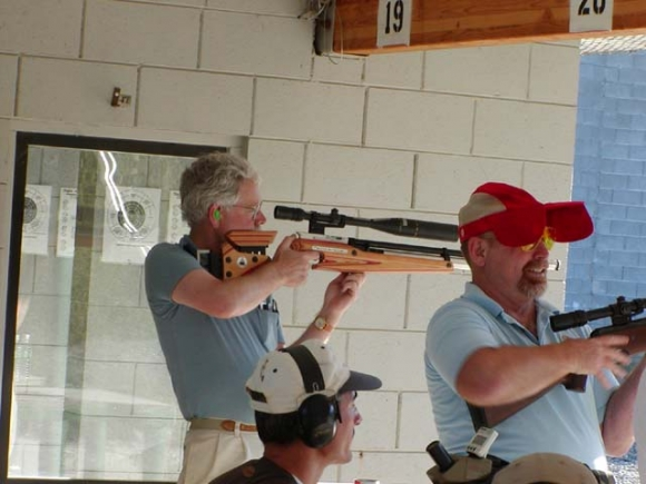 Bill Courington shoots while Chris Pfeiffer offers advice to Dan Theodore.