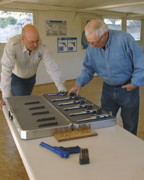 Two firearms trainers inspect an array of Ruger .22 pistols
