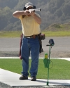 Trap shooter with shotgun mounted to shoulder