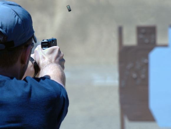 Action pistol shooter firing at silhouette target, with ejected shell in midair