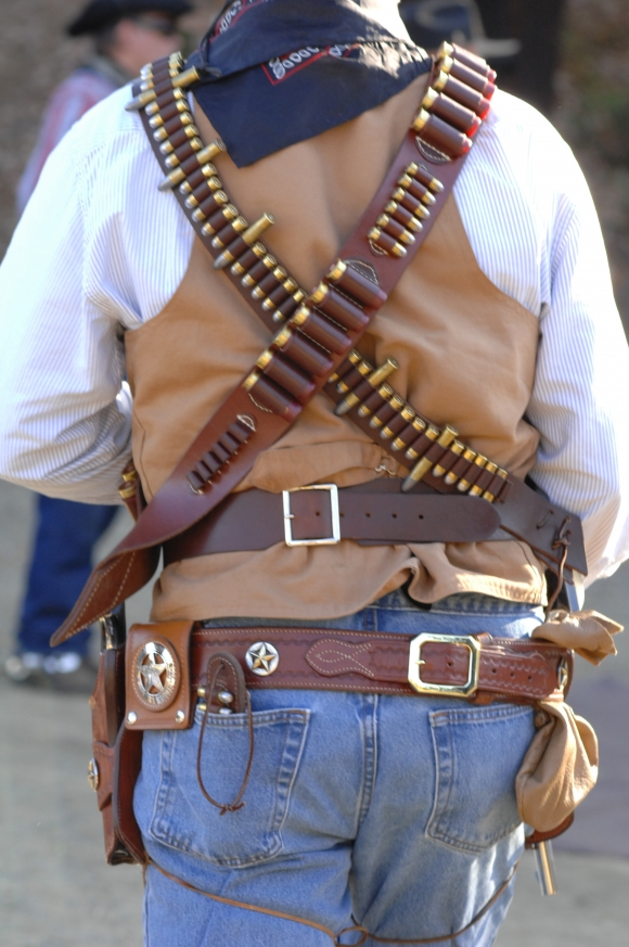 Cowboy shooter's torso from rear, showing crossed bandoliers loaded with ammo