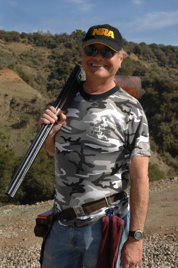 Shooter smiling at camera, with broken-open shotgun slung over right shoulder