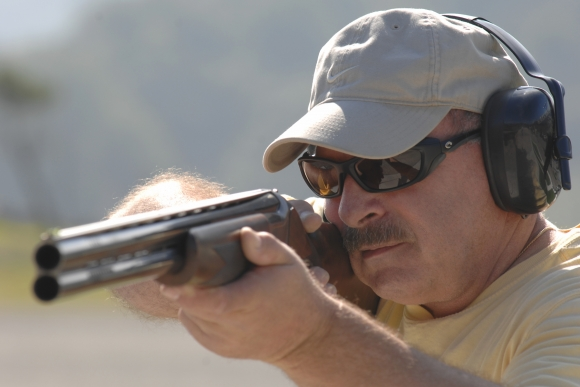 Close-up photo of man holding shotgun, from front