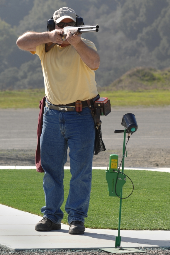 Full-body shot, from front, of right-handed shotgun shooter with gun at ready