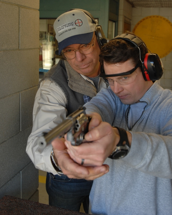 Shooter holding .22 revolver with two hands; instructor supports his grip