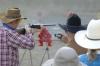 Cowboy shooter firing shotgun on left, range officer operating timer on right